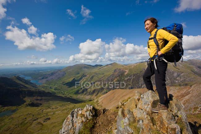 Hiker overlooking landscape standing on the rock - foto de stock