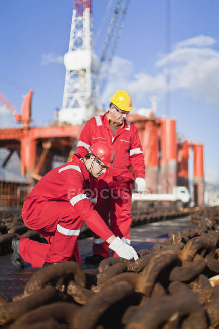 Рабочие на нефтяной вышке осматривают цепи — стоковое фото