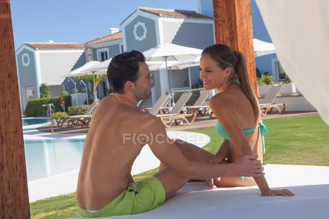 Young couple sitting on sunlounger at holiday resort — Stock Photo