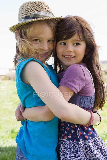 Улыбающиеся девушки, обнимающиеся на улице — стоковое фото