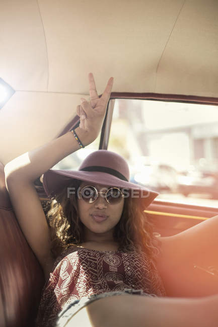 Young woman on road trip reclining in vintage car back seat making peace sign, Cape Town, South Africa — Stock Photo