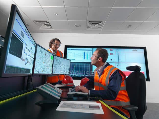 Lavoratori in sala di controllo con schermi — Foto stock