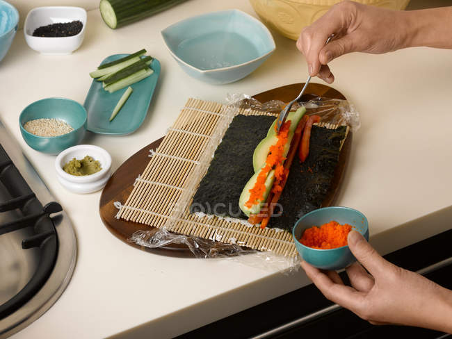Cropped image of Woman preparing sushi roll at table — Stock Photo
