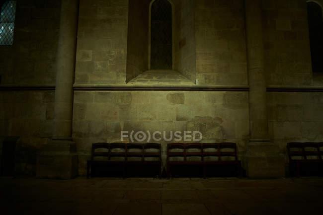 Bänke im dunklen Kirchenraum — Stockfoto