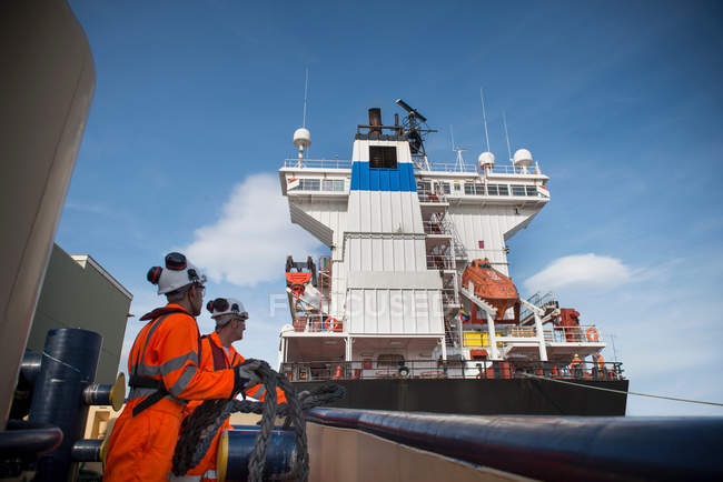 Operai rimorchiatori su rimorchiatore con nave container nelle vicinanze — Foto stock