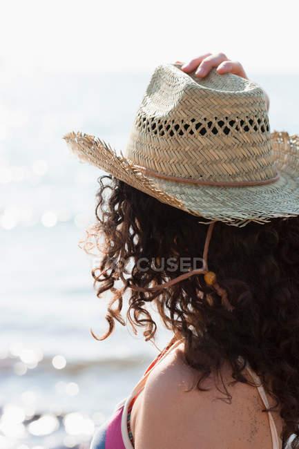 Visão traseira da mulher usando chapéu de sol na praia — Fotografia de Stock
