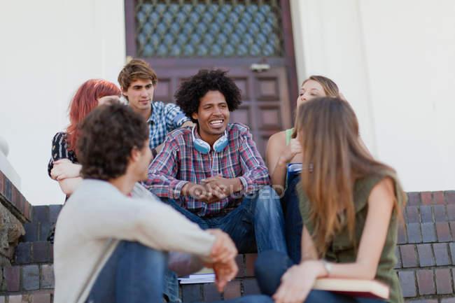 Estudiantes sentados juntos en el campus - foto de stock