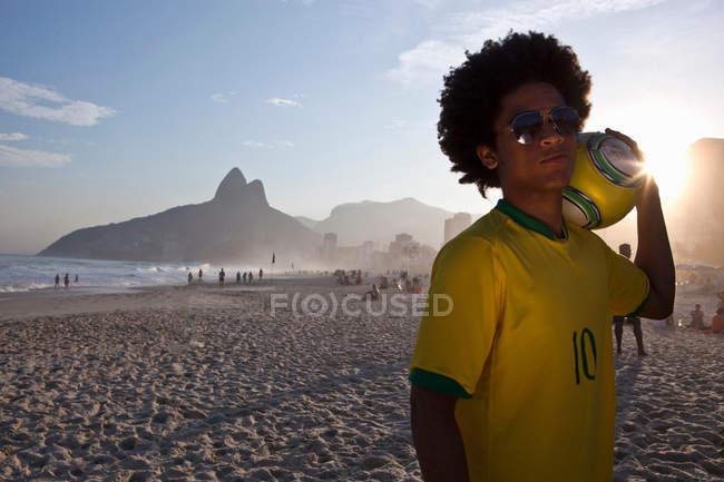 Young man at the beach with football, Ipanema Beach, Rio, Brazil — Stock Photo