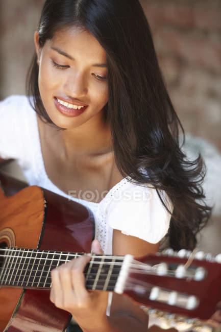 Porträt einer jungen Frau, die Gitarre spielt — Stockfoto