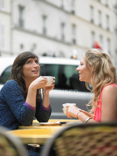 Жінки, які мають каву в тротуарі кафе — стокове фото