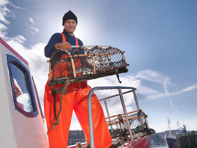 Pêcheur avec le pot de homard sur le bateau — Photo de stock