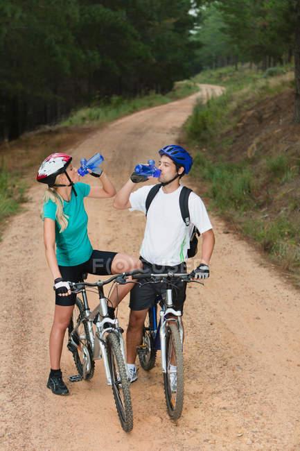 Пара питної води на гірських велосипедах — стокове фото