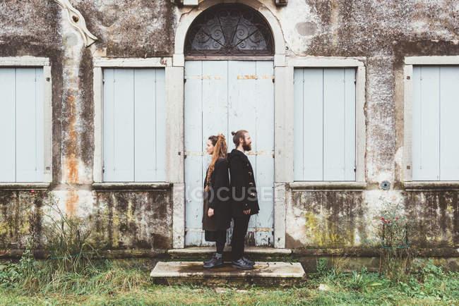 Ritratto di coppia in piedi dietro la porta della vecchia casa — Foto stock