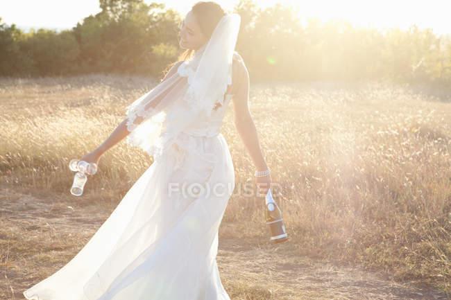 Novia recién casada llevando champán - foto de stock