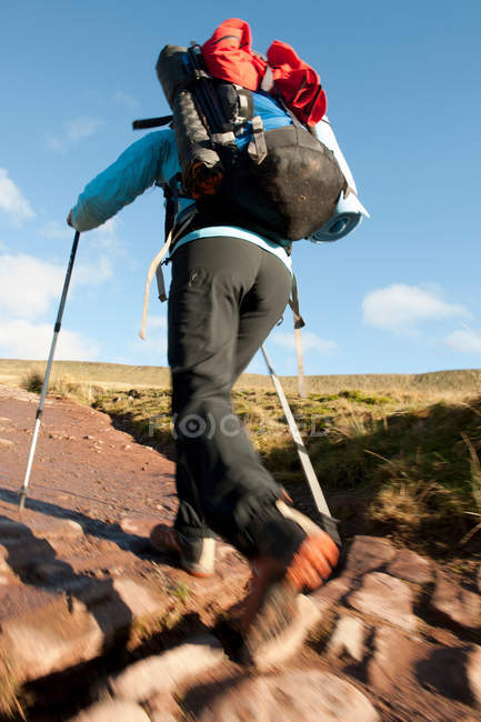 Hiker walking up rocky path — Stock Photo