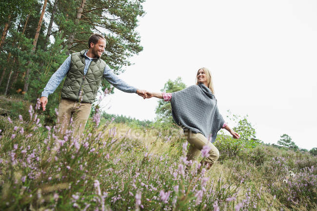 Mid adult couple holding hands in meadow — Stock Photo