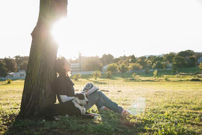 Donna rilassante con cane nel parco — Foto stock