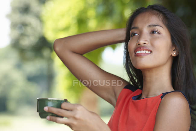 Portrait of young woman holding coffee cup with hand in hair — Stock Photo