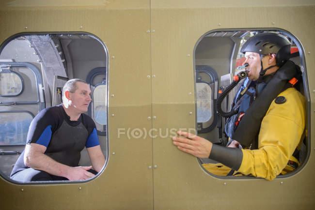 Travailleur pétrolier extracôtier en hélicoptère simulé, formé par un tuteur en survie au largage en mer, dans une installation de piscine — Photo de stock