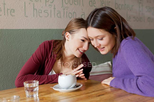 Le donne che si sussurrano in un bar — Foto stock