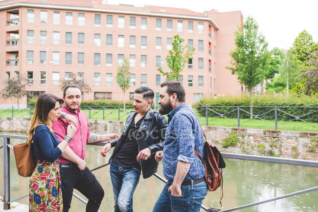 Group of friends chatting by river together — Stock Photo