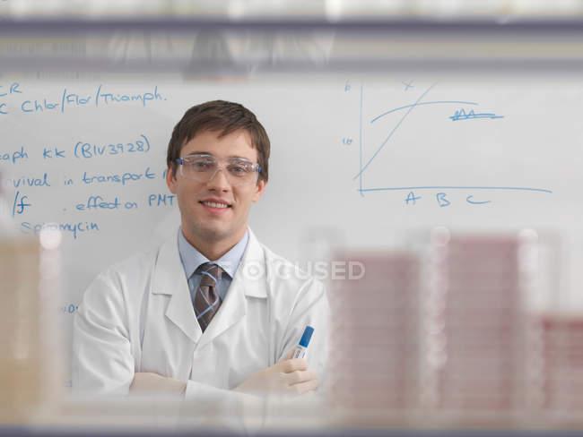 Portrait of Laboratory technician against whiteboard — Stock Photo