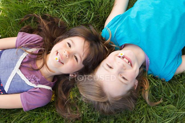 Sorridente ragazze posa in erba insieme — Foto stock
