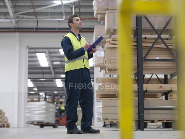 Trabajador con portapapeles en almacén - foto de stock