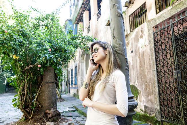 Молодая женщина разговаривает на смартфоне, Рио-де-Жанейро, Бразилия — стоковое фото
