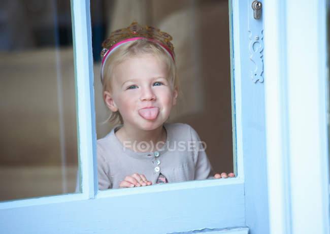 Menina criança em tiara fazendo rosto, foco em primeiro plano — Fotografia de Stock