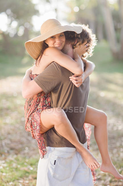 Smiling couple hugging in field — Stock Photo