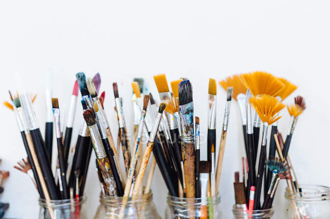 Still life of glass jars containing paintbrushes — Stock Photo