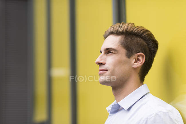 Portrait of young businessman leaning outside office, London, UK — Stock Photo