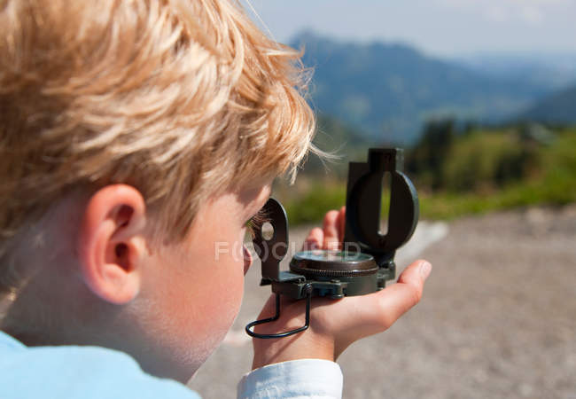 Close up of Boy using compass outdoors — Stock Photo