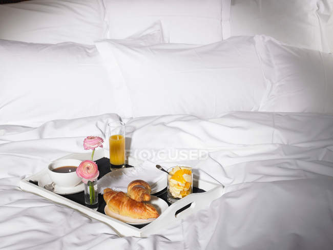 Breakfast tray with coffee cup and croissants in bed — Stock Photo