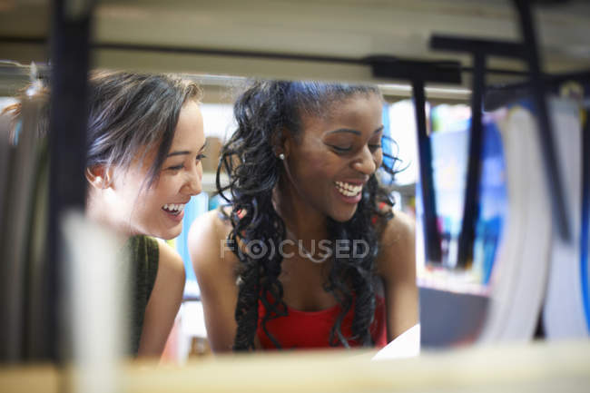 Two young female college students looking on library shelves — Stock Photo
