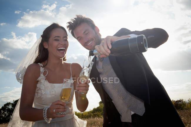 Молодят, маючи шампанське — стокове фото