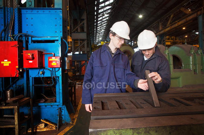 Workers examining metal in steel forge — Stock Photo