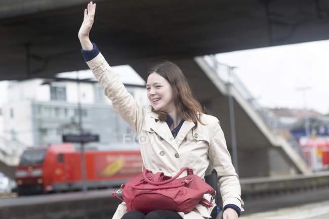 Молода жінка, використовуючи візку розмахуючи від залізничного вокзалу міста — стокове фото