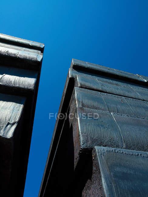 Вигляд знизу сталі заготовок проти синього неба — стокове фото