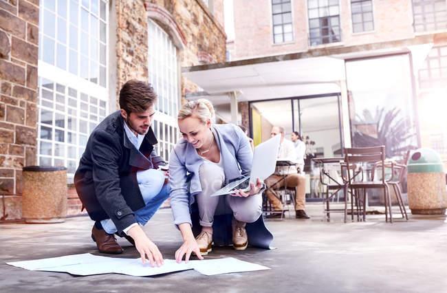 Бизнесмен и мужчина рассматривают документы на полу в патио офиса — стоковое фото