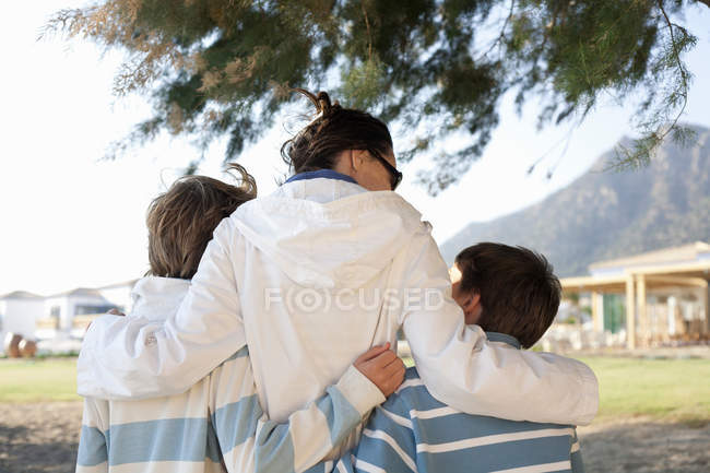 Mother with arms round two sons — Stock Photo