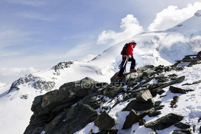 Человек, поднимающийся на заснеженную гору, Саас-Фи, Швейцария — стоковое фото