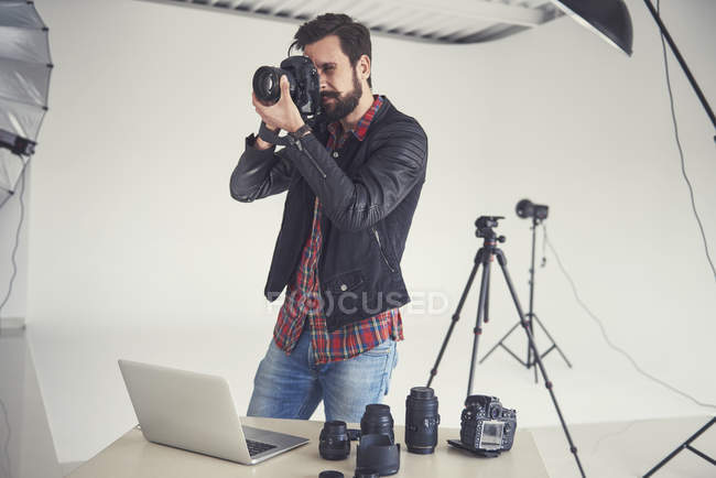 Male photographer testing digital SLR focus for studio photo — Foto stock