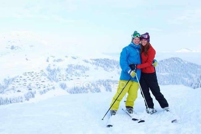 Лыжники обнимаются на заснеженной вершине горы — стоковое фото