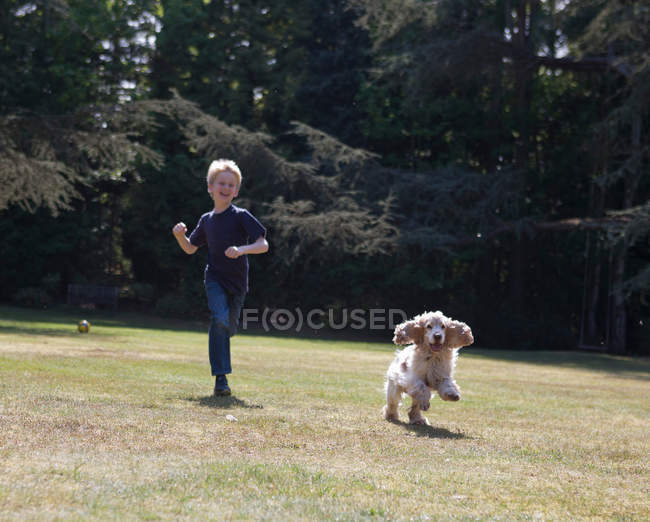 Garçon jouer avec chien dans la cour arrière — Photo de stock