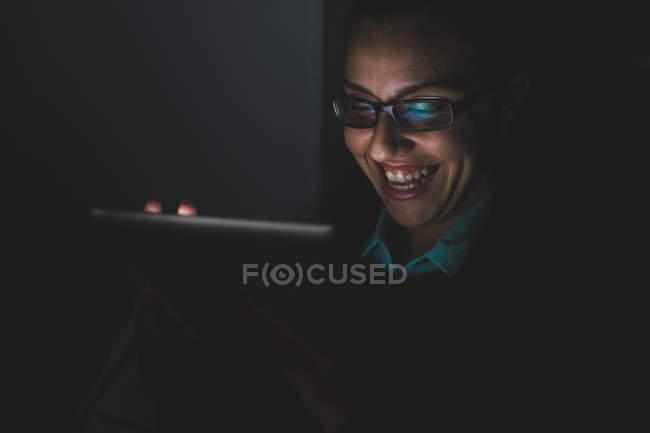 Молодая женщина смеется при использовании цифрового планшетного сенсорного экрана в темноте — стоковое фото