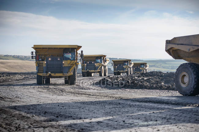 Dumpers driving on track at surface coal mine — Stock Photo