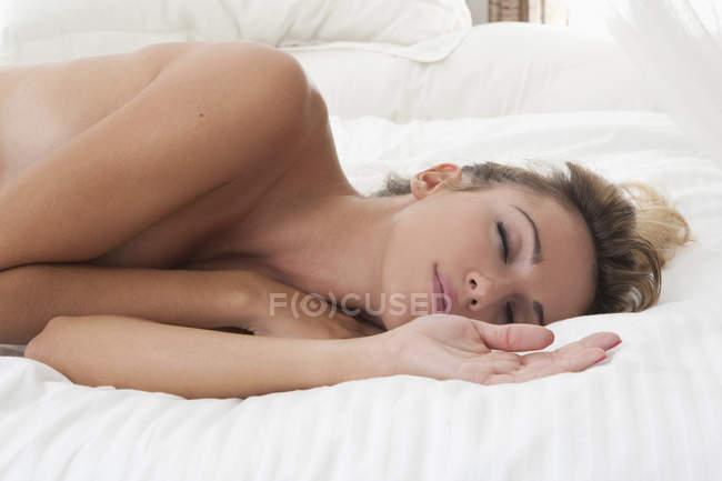 Оголена спить на ліжку — стокове фото