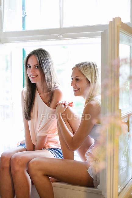 Donne sorridenti sedute nel davanzale della finestra — Foto stock
